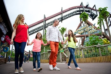 Family Walking Through Jungle Area Of The Theme Park